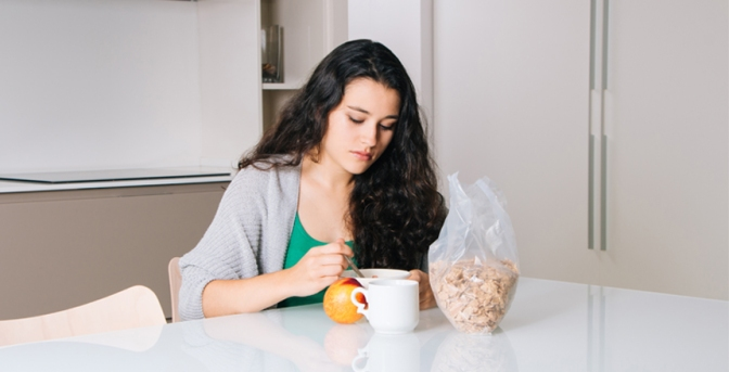 Sad young woman having breakfast